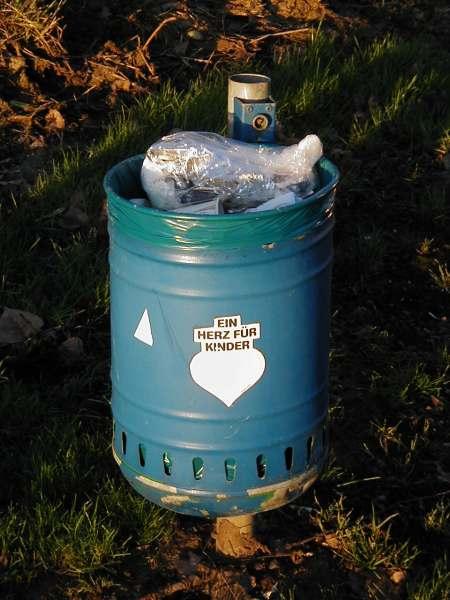Foto einer blauen Mülltonne auf einem Parkplatz, die bis an den Rand gefüllt ist. Auf dieser Mülltonne klebt ein stark ausgeblichener Aufkleber 'Ein Herz für Kinder'.